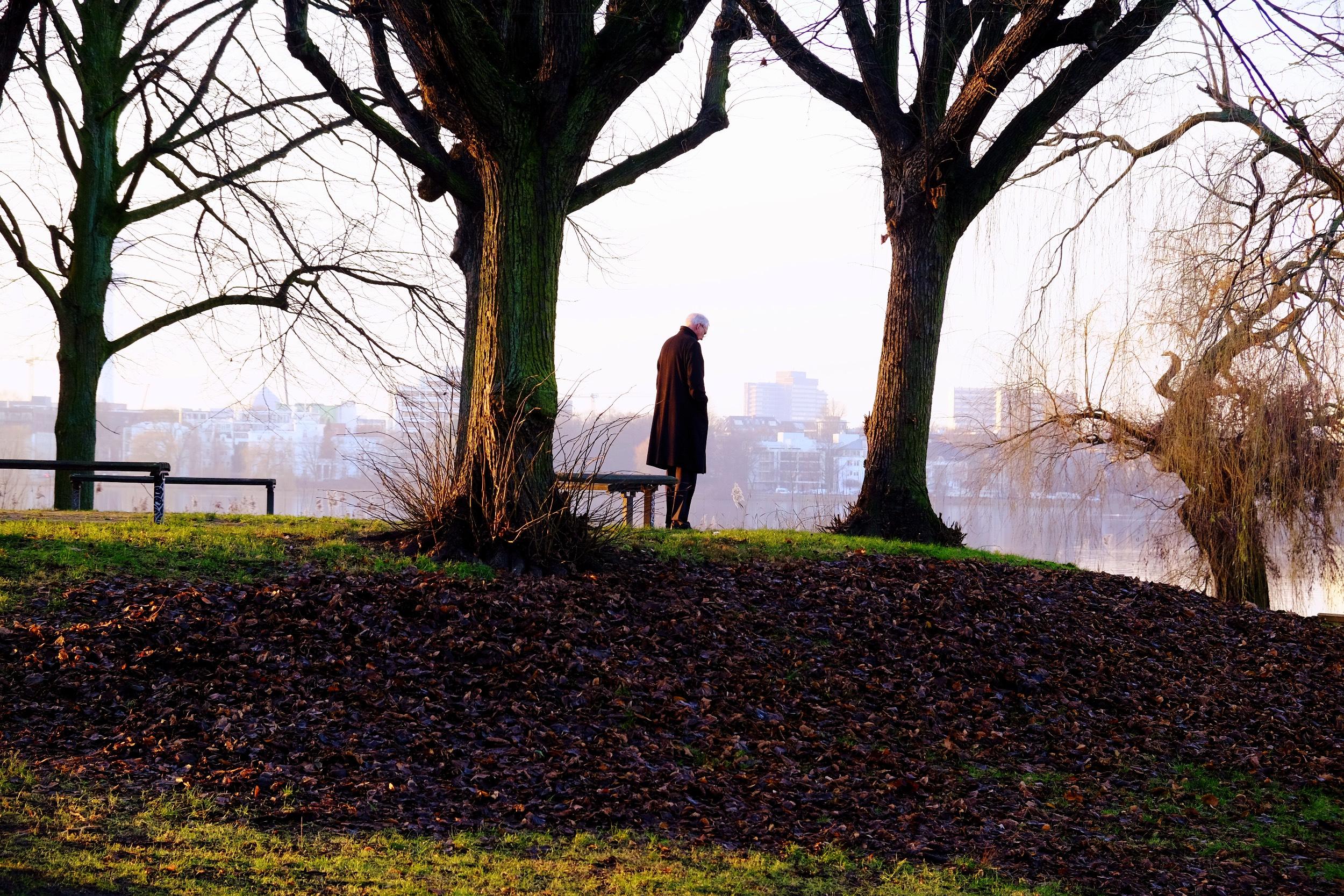 Ein Mann steht alleine an der Alster